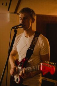 Irish Indie-pop artist Fintan McKahey plays the guitar singing into the mic