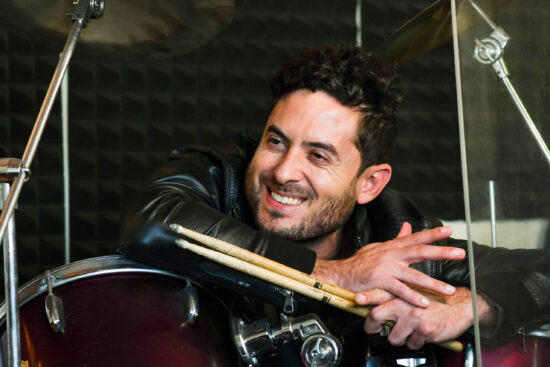 Smiling musician Wes David leaning on his drum kit